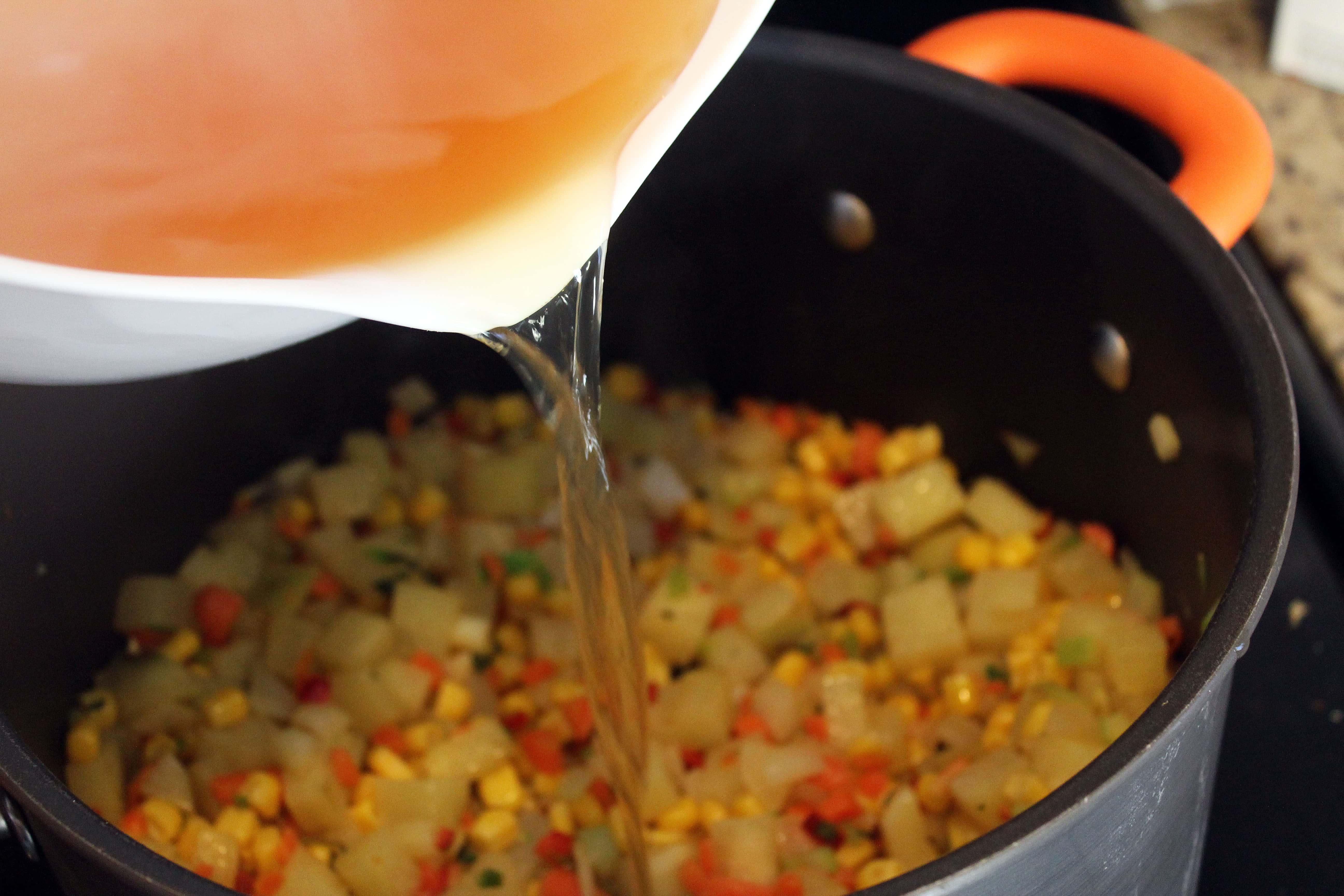 Add stock to sauteed veggies