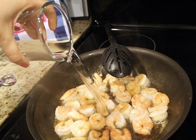 Add wine to half cooked shrimp