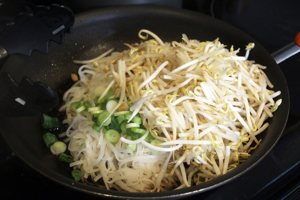 Add bean sprouts and scallions to noodle pan