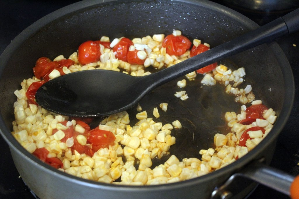 Add corn to tomatoes and stir